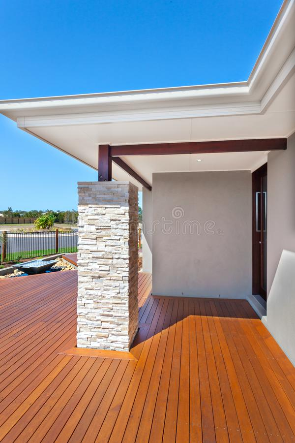 Modern house entrance from the side with wooden floor and a stone pillar like a brick wall. Luxury house with a blue sky background without clouds in behind stock photography