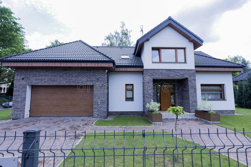 Modern house exterior with brick walls. Modern house exterior with the garden and brick walls and chain-link fence royalty free stock image