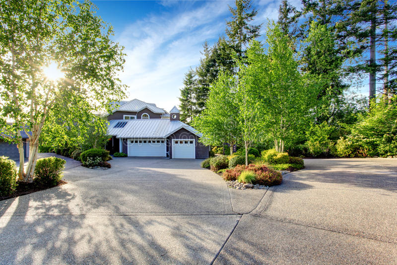 Modern house exterior with curb appeal. View of garage and spacious driveway royalty free stock photos