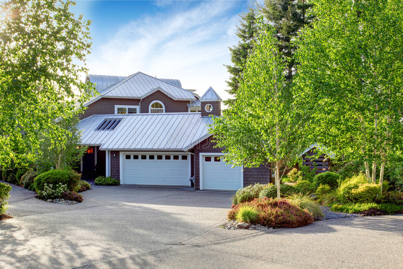 Modern house exterior with curb appeal. View of garage and spacious driveway royalty free stock image