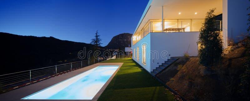 Modern villa, exterior in the night, lights on stock photos