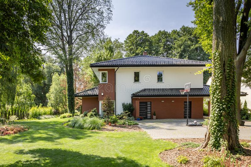 Modern house, garden with bushes and trees stock photos