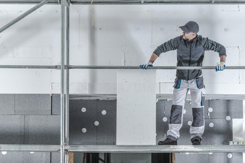 Modern House Insulation. Construction Worker Installing Molded Graphite Polystyrene royalty free stock images