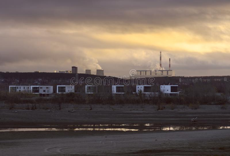 Modern houses on the bank of the Ob River near Novosibirsk. Modern houses on the sandy bank of the Ob River. Thermal Power Station on the horizon in the rays of royalty free stock photos