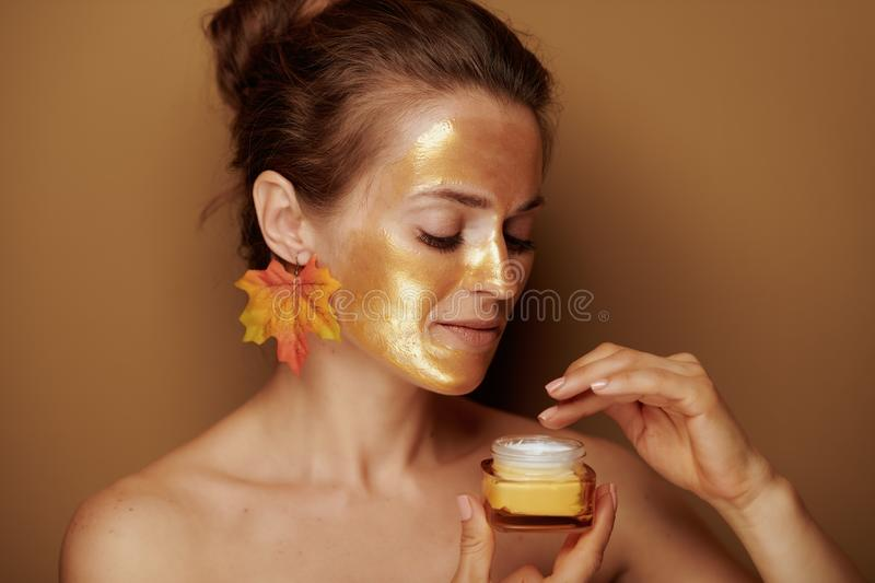 Modern housewife with golden mask using cosmetic product royalty free stock images