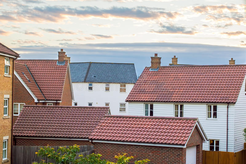 Modern housing estate UK. Variety of homes and garages against c stock image