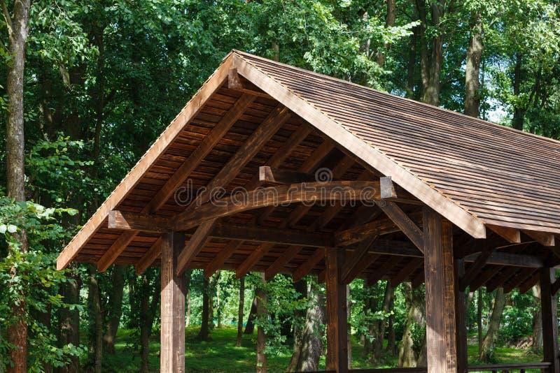 Modern houten dak, luifel, op een achtergrond van groene bomen stock foto's