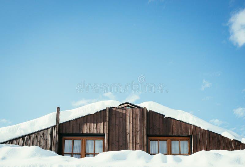 Modern houten huis met vensters en sneeuw op het dak, blauwe hemel met tekstruimte royalty-vrije stock afbeeldingen