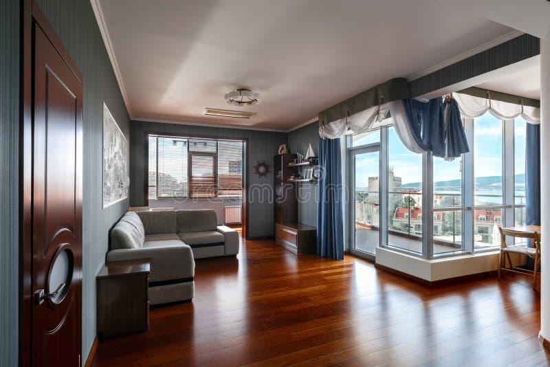 Modern huis, een woonkamer met het moderne meubilair en een schilderachtige mening van de stad stock foto