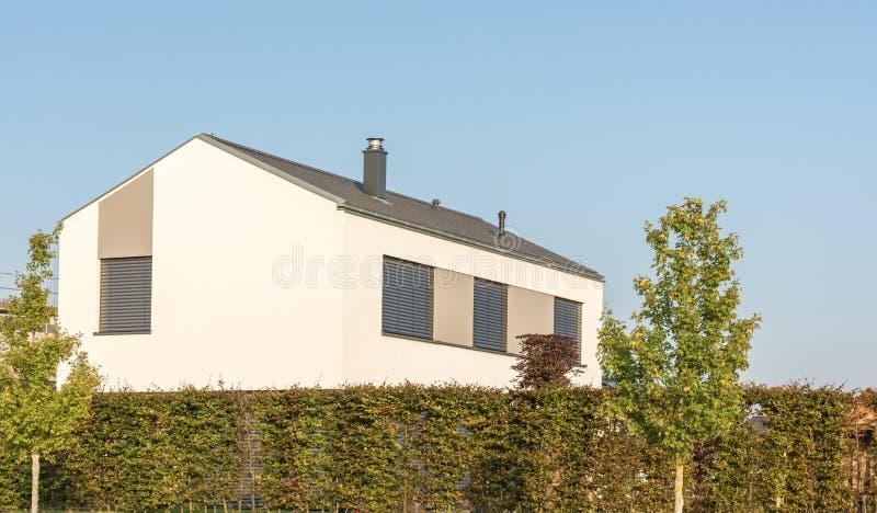 Modern huis met buitenzonneblinden met hoge haag als privacy stock afbeelding