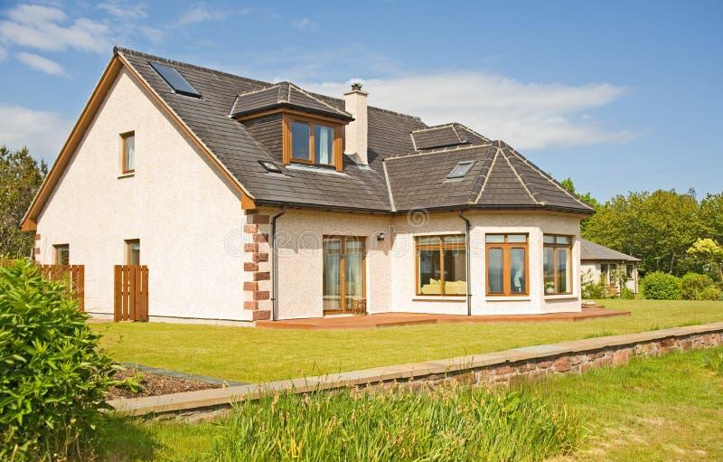 Modern huis met schoorsteen en tuin. stock foto