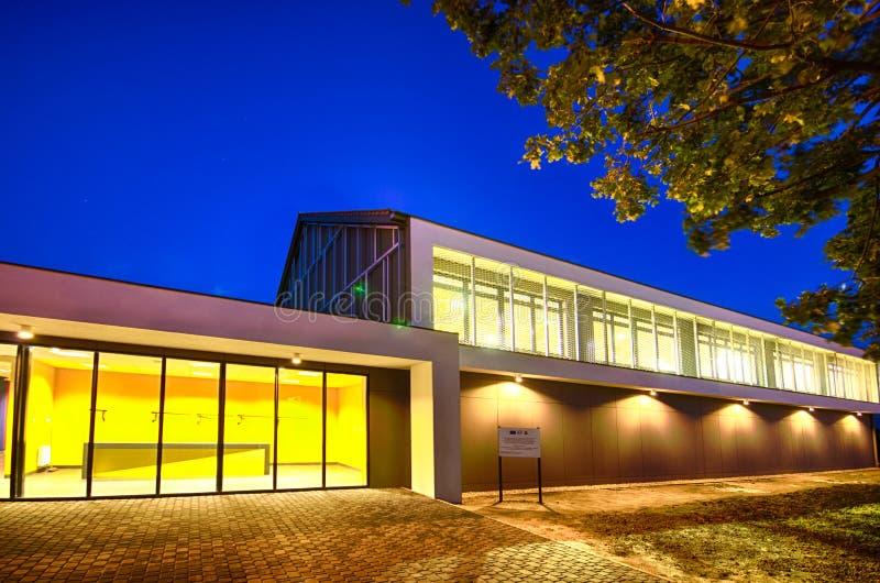 Modern idrottshallbyggnad på natten arkivbilder