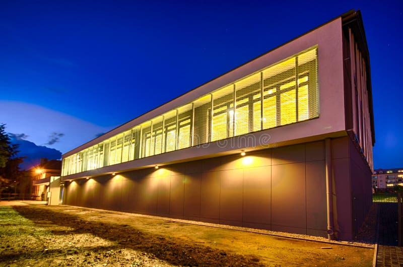 Modern idrottshallbyggnad på natten fotografering för bildbyråer