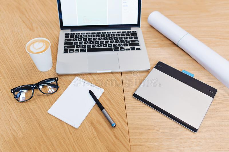 Modern image of work stuff on table from above view. Laptop, black glasses, pencil, notebook, coffee, designing stock photography