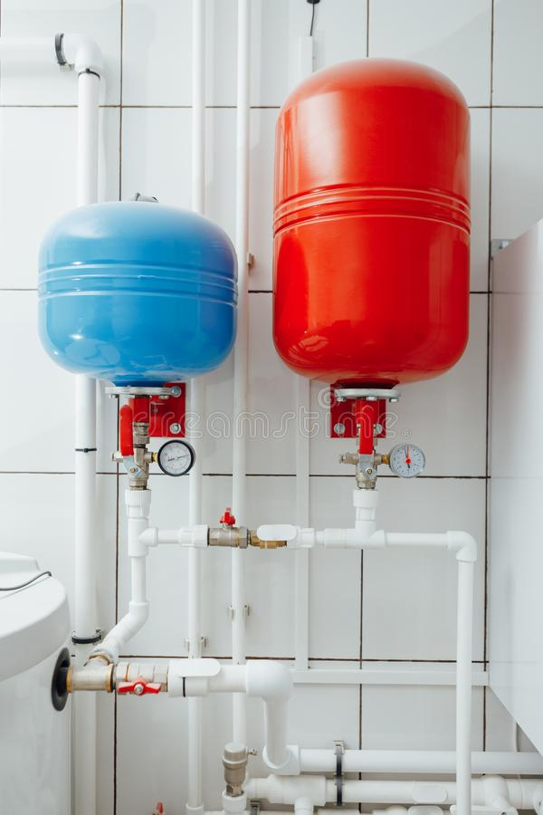 Modern independent heating system in boiler room. Blue and red expansion tanks royalty free stock images