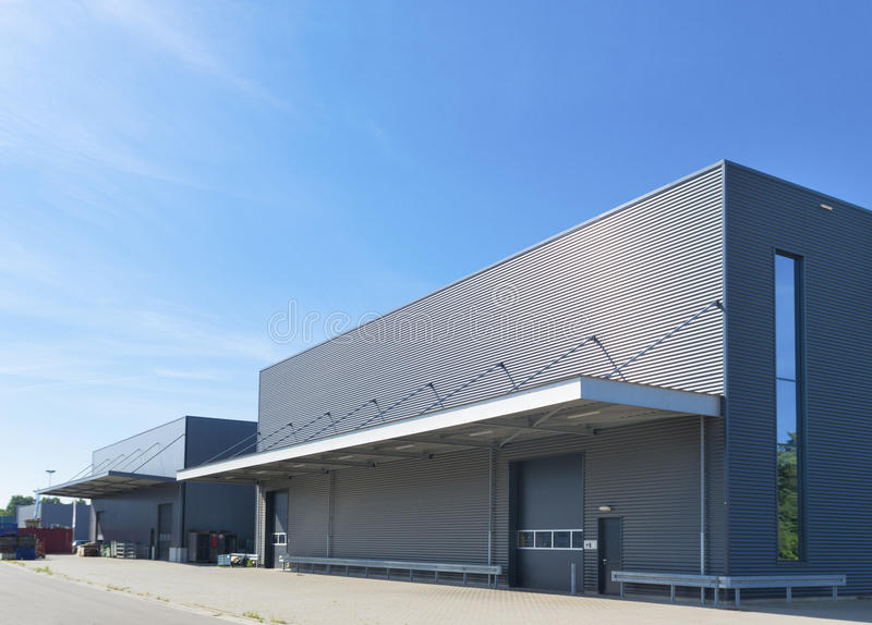 Modern industrial building. Exterior of a modern warehouse building against a blue sky royalty free stock photography