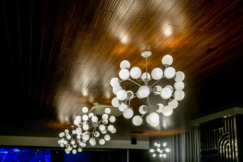 Modern and industrial style lamps in the interior of a beauty salon or restaurant. Chandeliers with bubble shade. Loft-style stock photography