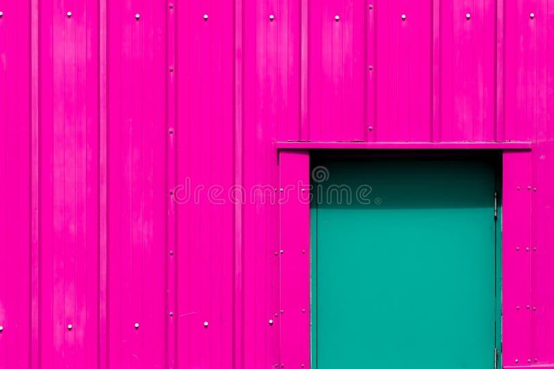 Modern industrialism Rosa byggnad för neon med den gröna dörren Vibran arkivfoto