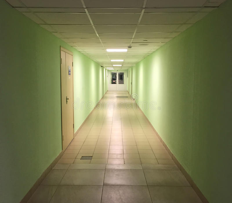 Modern inre i regeringsställning som bygger Lång tom korridor med avlägsna dörrar och kontorsingången royaltyfria bilder