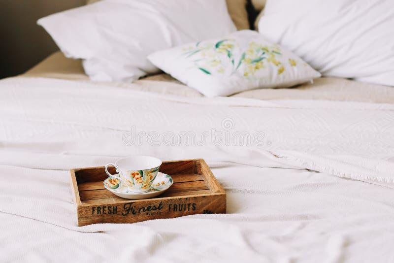 Modern inredningsdesign i hemmet Cozy bed med träpåk och kuddar, filt Inredning i sovrum, skandinaviskt royaltyfri fotografi