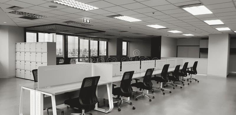 Modern inredningsdesign med radsvarta stolar och träbord med fönster- och byggbakgrund i svartvitt t arkivfoto