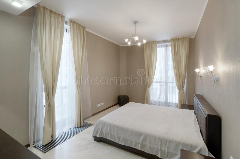 Modern interior of a bedroom in the new house. Stylish bedroom interior with double bed royalty free stock photography
