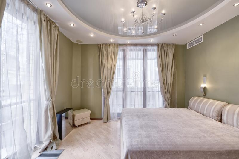 Modern interior of a bedroom in the new house. Stylish bedroom interior with double bed stock photography