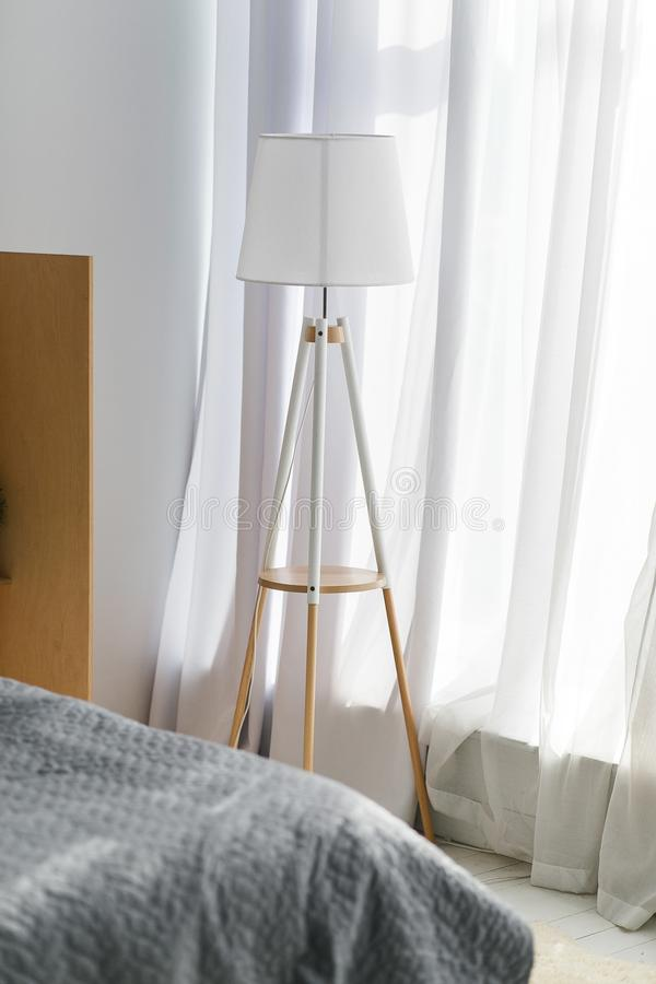 Modern interior of a bedroom in the new house. White lamp standing on the floor near window covered with tulle curtains royalty free stock photography