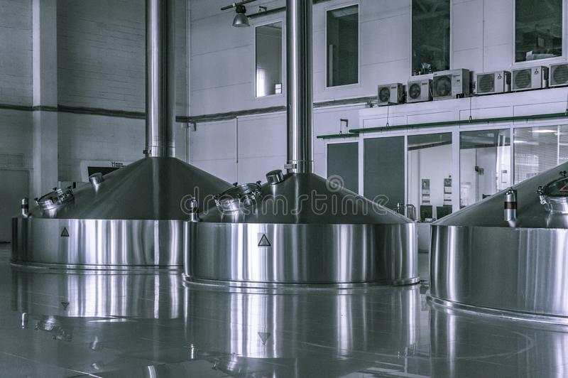 Modern interior of a brewery mash vats metal containers. Modern interior of a beer factory mash vats metal containers royalty free stock photos