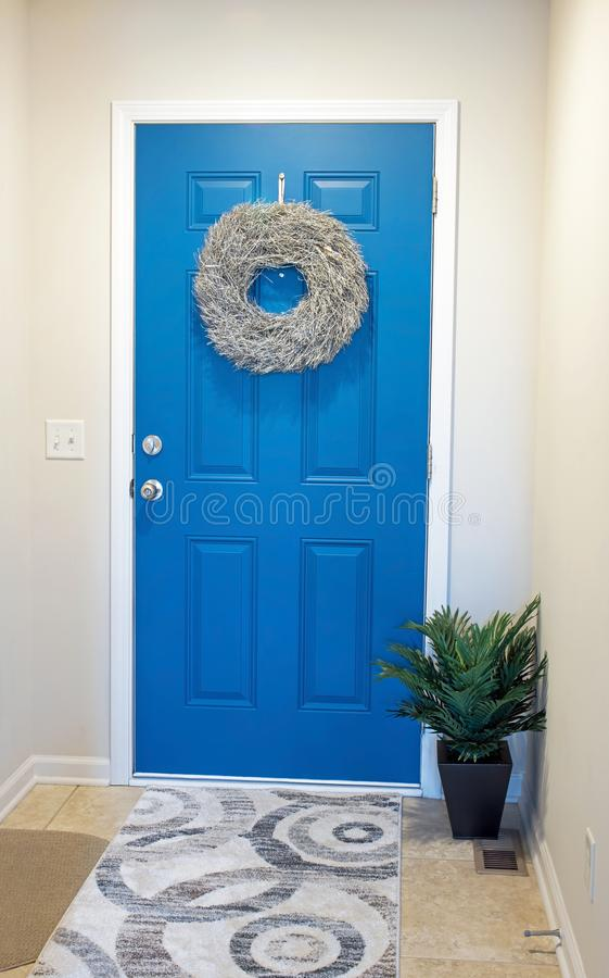 Blue Door with Gold Twig Wreath. Modern, interior, blue, entry door with gold. twig wreath & potted fern stock image
