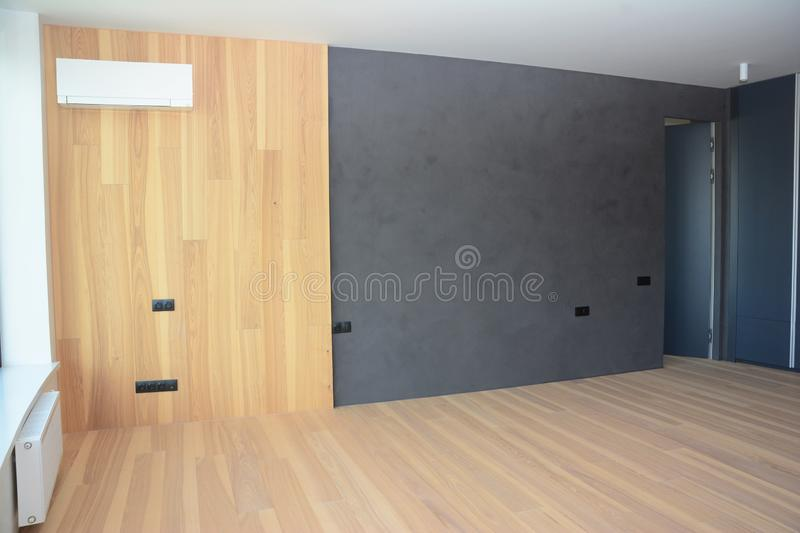 Modern interior house room with wooden floringa, wooden wall decoration, radiator and air conditioning royalty free stock images