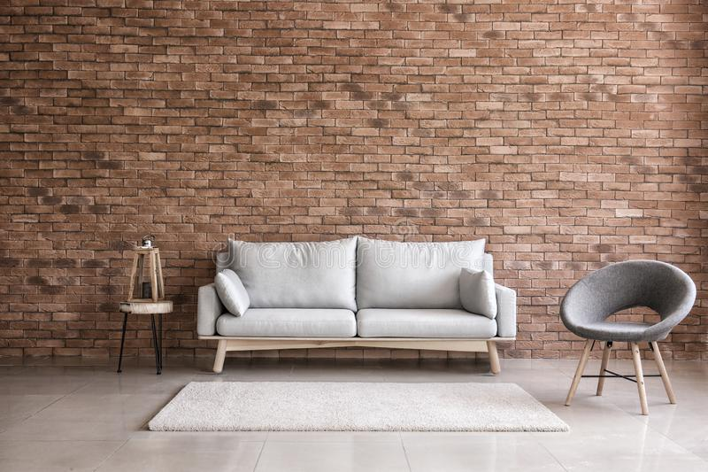 Modern interior of living room with comfortable sofa and armchair near brick wall stock images
