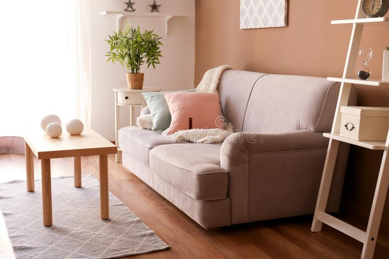 Modern interior of living room with comfortable sofa and wooden table royalty free stock images