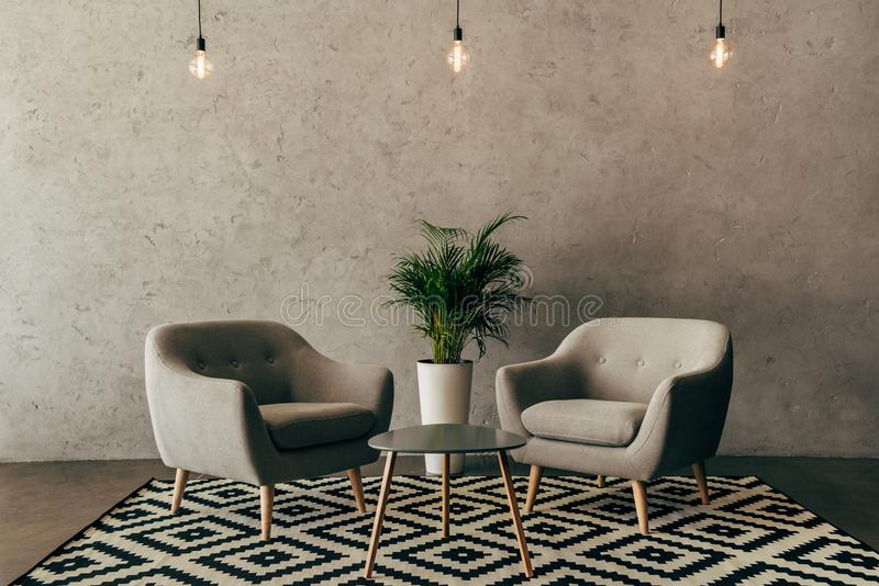 Modern interior with vintage furniture in loft style with concrete wall. On background royalty free stock photography