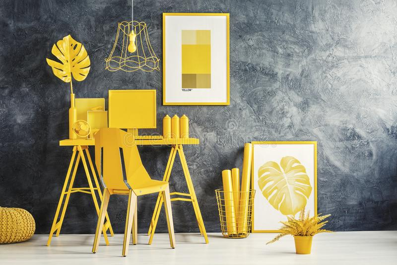 Modern interior with yellow desk. Modern interior with computer, plant, candles on a yellow desk and posters on the wall royalty free stock image
