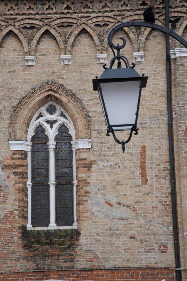 Modern iron and glass bollard and Gothic style window. View of a public lamppost from the Accademia bridge towards the church of Santa Maria della Carita State stock image