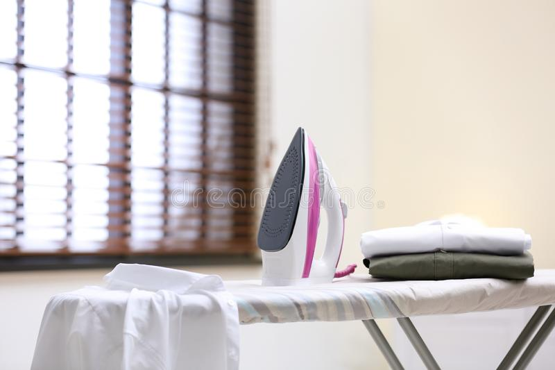 Modern iron and shirts on board royalty free stock photography