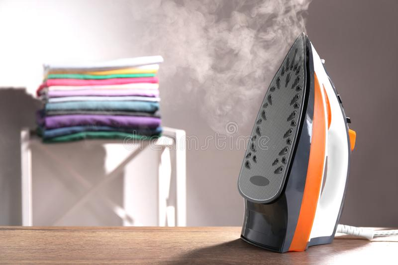 Modern iron with steam on table indoors royalty free stock image