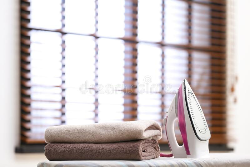 Modern iron and towels on board royalty free stock photo