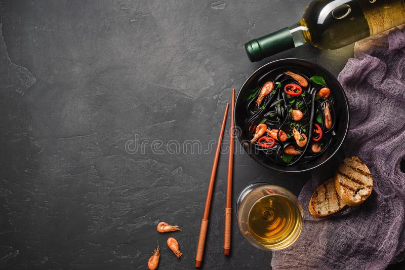 Modern japanese dinner, Mediterranean food, black cuttlefish ink spaghetti pasta with seafood, olive oil and basil, on dark rusty royalty free stock image