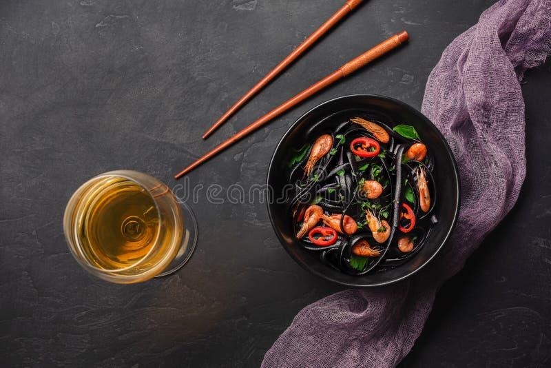 Modern japansk matställe, medelhavs- mat, svart pasta för bläckfiskfärgpulverspagetti med skaldjur, olivolja och basilika, på mör royaltyfri bild