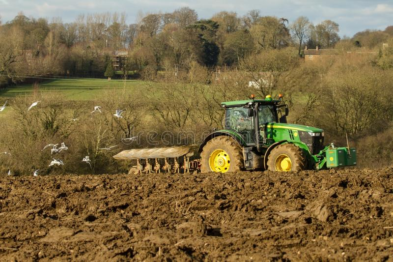 Modern John Deere tractor pulling a plough followed by gulls. Green modern John Deere tractor ploughing a field with plough working field followed by gulls stock image