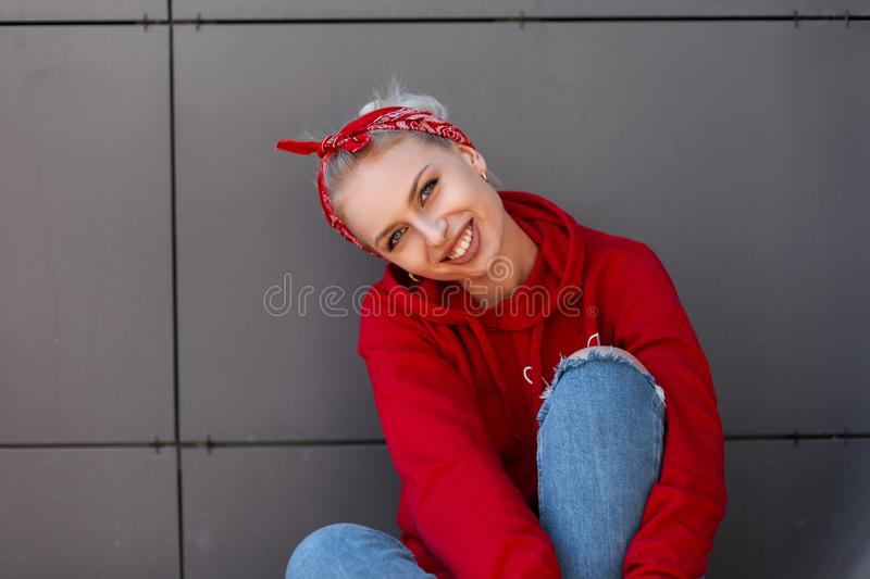 Modern joyful young woman with a cute smile in modern fashionable clothes with a red bandanna is resting. Near a gray vintage building on a warm summer day stock photography
