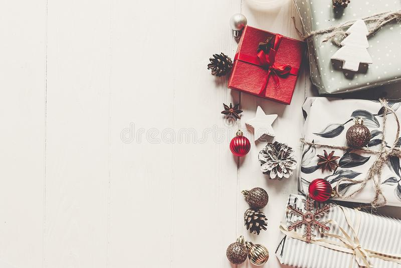 Modern jul slogg in gåvor med prydnader och kottar på wh royaltyfri bild