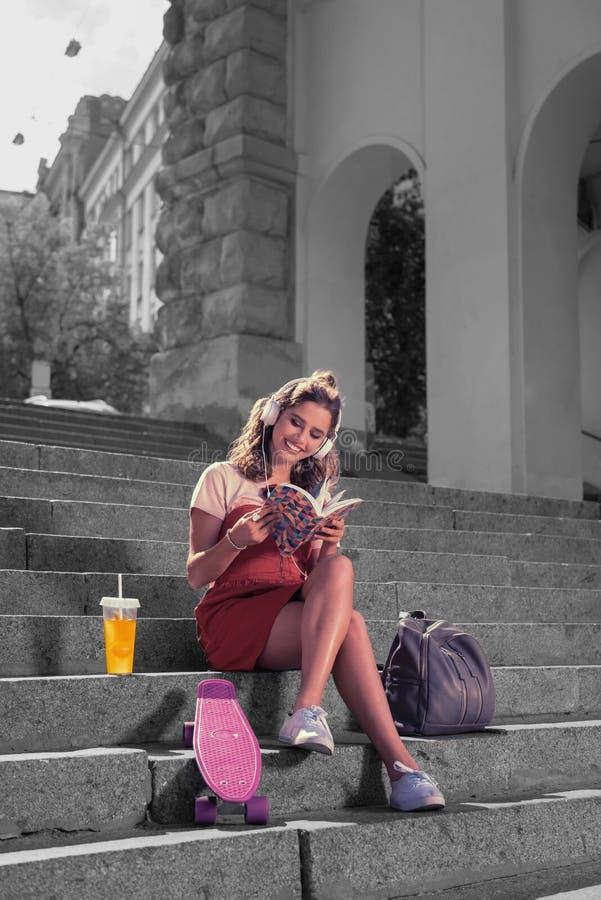 Modern känsla för den kvinnliga studenten som är lycklig, når den har skateboarding med hennes vänner i, parkerar fotografering för bildbyråer