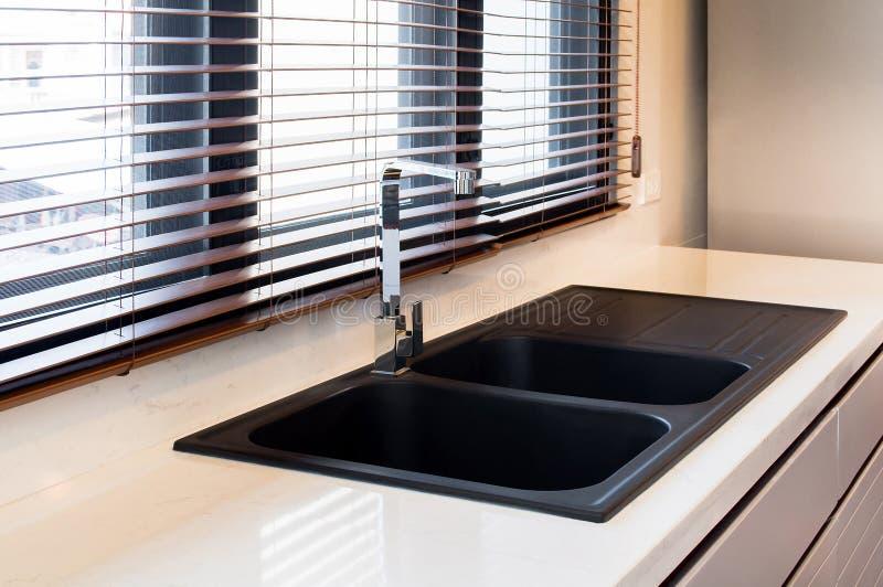 Modern kökinre i stadslägenheten Vit marmor, kök för kvartsräknareöverkant med den svarta vasken och vattenkran, träblind sol royaltyfri bild