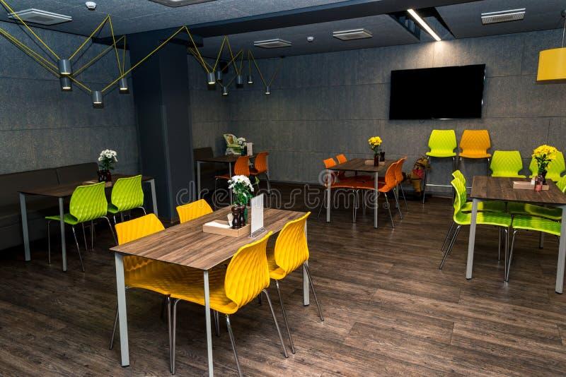Modern kaféinre, färgrik tabell och stolar arkivbild