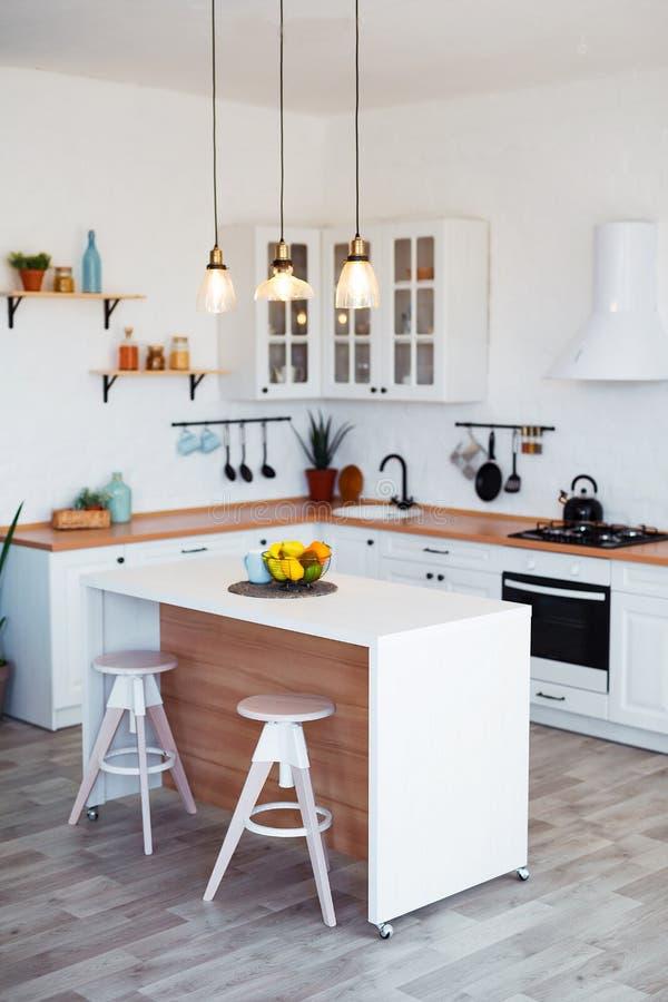 Modern Keukenbinnenland met Eiland, Gootsteen, Kabinetten, en Groot Venster in Nieuw Luxehuis stock foto