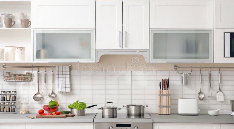 Modern keukenbinnenland met houseware en meubilair stock afbeeldingen