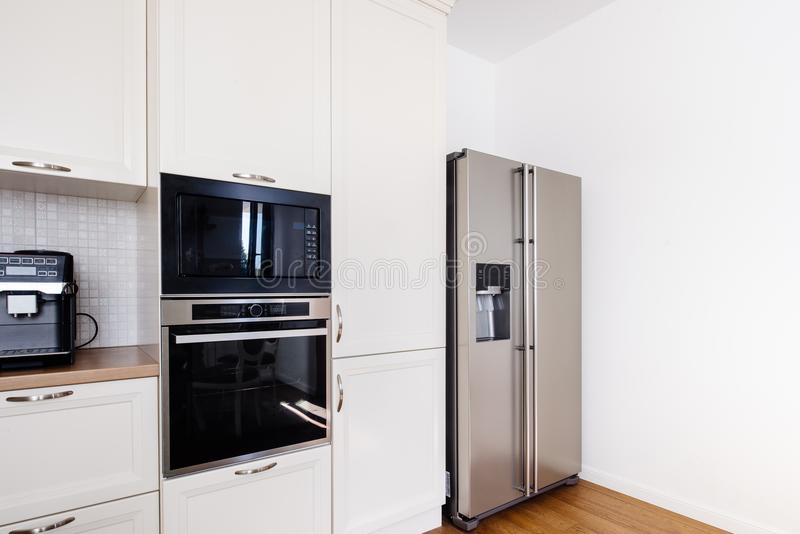 Modern keukengebied, houten vloer met moderne ijskast en toestellen stock afbeelding